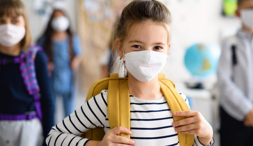 young girl wearing mask and backpack addresses camera in a school setting