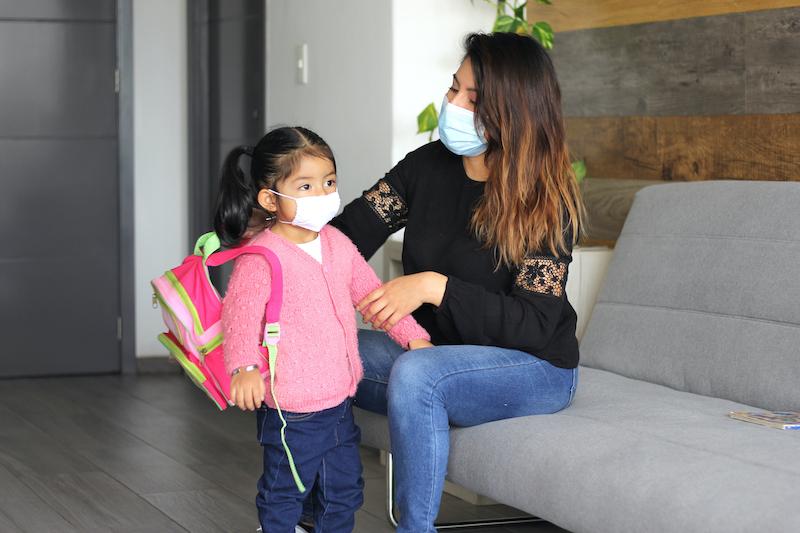 Mother wearing medical mask helping daughter wearing medical mask with her backpack
